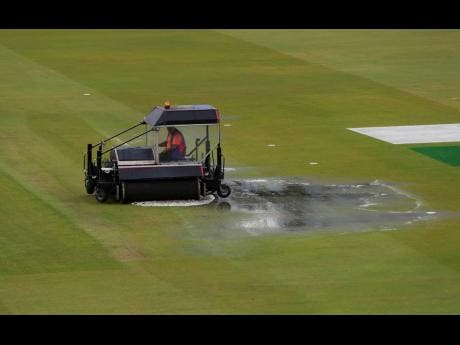 A super sopper is used to remove water after rain stopped play during the Cricket World Cup semi-final match between India and New Zealand at Old Trafford in Manchester, England, yesterday.