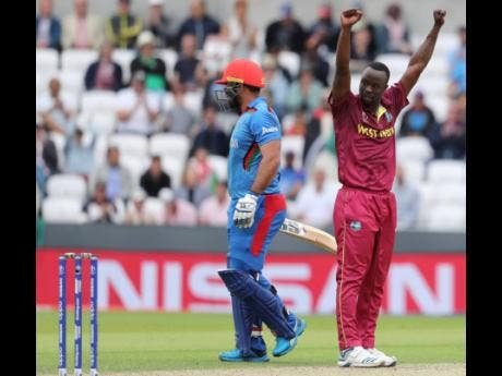 West Indies' Kemar Roach (right) celebrates the dismissal of Afghanistan's Samiullah Shinwari (left) during the Cricket World Cup.