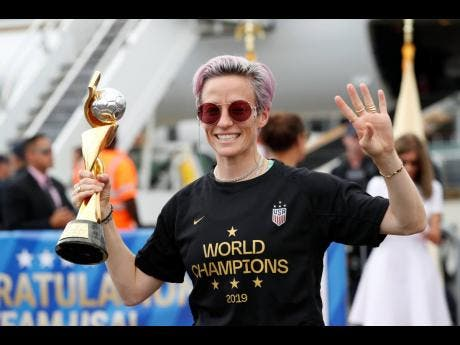 United States women's soccer team member Megan Rapinoe holds the Women's World Cup trophy as she celebrates in front of the media after arriving at Newark Liberty International Airport on Monday.