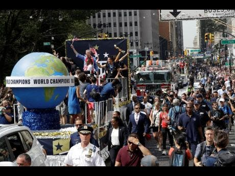 A float with members of the US senior women's football team and New York Mayor Bill de Blasio (left, back of the trucks) makes its way up Broadway in a ticker-tape parade along the Canyon of Heroes in New York City yesterday.