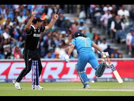 New Zealand's Colin de Grandhomme (left) celebrates the run-out of India's Mahendra Singh Dhoni during their ICC World Cup semi-final match at Old Trafford in Manchester, England, yesterday.