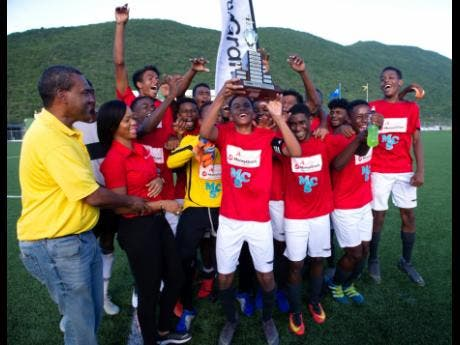 KSAFA president Wayne Shaw and Devonna Coke, senior operations officer at Alliance Investment, present the trophy to members of the Real Mona  team after they won the Alliance MoneyGram KSAFA U-17 title.
