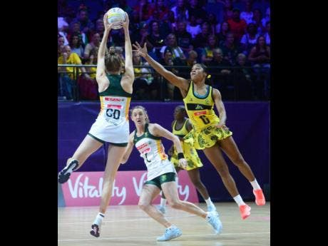 Jamaica's Adean Thomas challenges for the ball as South Africa's Karla Pretorius (GD) tries to pass it to her teammate, Erin Burger (C).