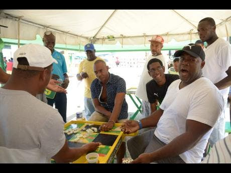 Fans enjoy a game of dominoes during the interval at the SDC Wray & Nephew T20 Community Cricket feature match yesterday.