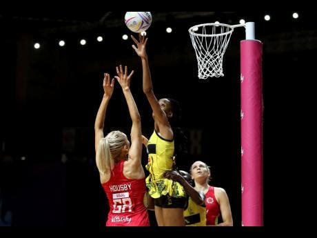 England's Helen Housby (left) and Jamaica's Shamera Sterling (top) battle for the ball during the Netball World Cup.  AP photos