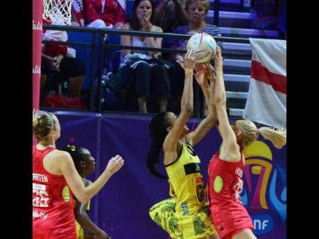 Romelda Aiken reaches for the ball as England's Geva Mentor challenges.