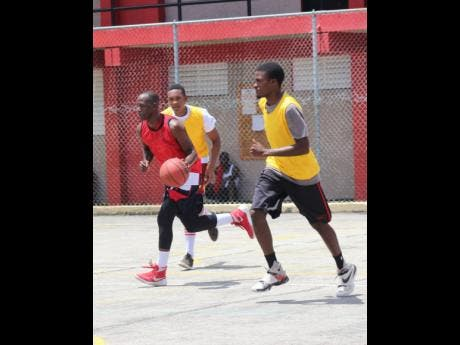 Dave Black (left) in action for St James in a Social Development Commission competition game against St Ann.