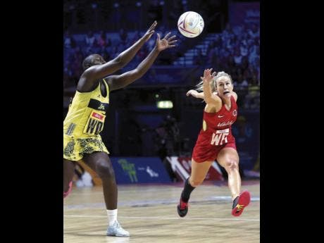 Photo By Nigel French England's Chelsea Pitman (right) tries to reach Jamaica's Vangelee Williams during the Netball World Cup match in Liverpool, England, on Monday.