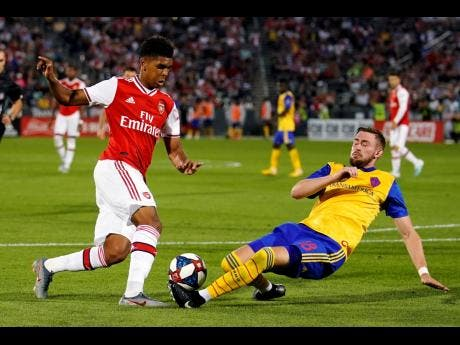 Colorado Rapids defender Sam Raben (right) slides in to try and steal the ball against Arsenal midfielder Gabriel Martinelli during the second half of an international friendly match on Monday. AP