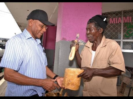 Clement Clunis (left) purchases a mortar and pestle set from Brisette.
