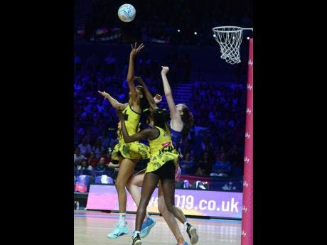Jamaica's Shamera Sterling (left) and Jodian Ward (centre) get tangled with Scotland's Emma Barrie as they go up to collect a pass during their Group G Vitaly Netball World Cup game at the M&S Bank Arena in Liverpool, England, yesterday. Photos courtesy of Collin Reid, Courts Jamaica, Jamaica Tourist Board, Alliance Investments, Dairy Industries, and Supreme Ventures.