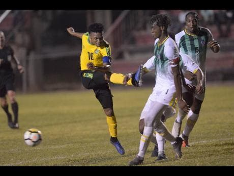 Jamaica's Alex Marshall (left) shoots but his shot is blocked by Dominica defender Mitchel Gylles (centre) during their Caribbean Football Union Olympic Qualifying match at the Anthony Spaulding Sports Complex in Kingston last night.