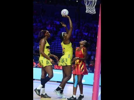 Jamaica captain Jhaniele Fowler (centre) shoots ahead of Uganda's Muhayimina Namuwaya (right) as Romelda Aiken covers during their Vitality Netball World Cup game at the M&S Bank Arena in Liverpool, England, on Thursday. Photos courtesy of Collin Reid, Courts Jamaica, Jamaica Tourist Board, Alliance Investments, Dairy Industries, and Supreme Ventures.