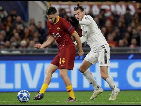 In this file photo Tuesday, November 27, 2018 filer, Roma defender Kostas Manolas (left) and Real midfielder Gareth Bale vie for the ball during a Champions League, Group G match between Roma and Real Madrid at the Rome Olympic stadium.