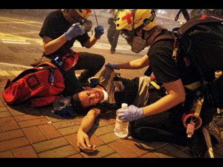 Medical workers help a protester in pain from tear gas fired by policemen on a street in Hong Kong yesterday.
