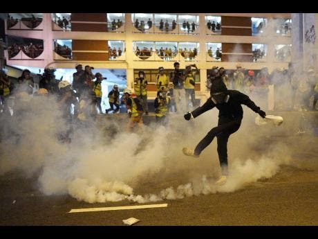 A protester kicks a tear gas canister during confrontation in Hong Kong yesterday.