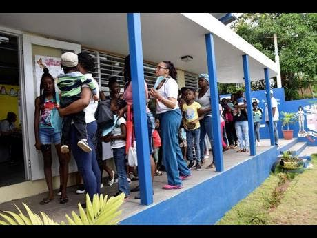 Residents of the Brandon Hill  community in Clarendon, patiently wait to be seen by the medical team.
