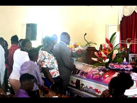 Relatives and well-wishers line up to view the body of Janice Cummings during her funeral at the Chatham Seventh-day Adventist Church in Blytheston, St James, on Sunday.