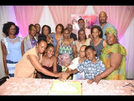Family members and friends join Evelyn Stanley for the cutting of the cake.