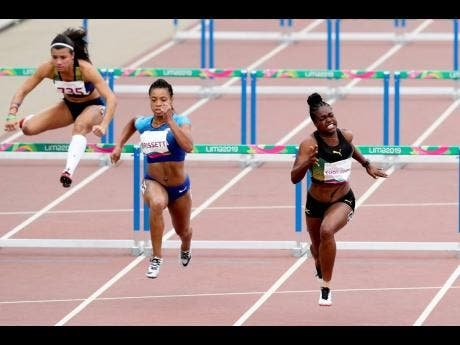 Yanique Thompson of Jamaica makes the final effort to win her semi-final in the women's 100m hurdles yesterday.