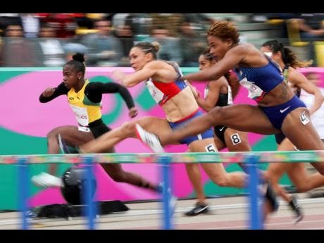 Megan Simmonds of Jamaica (left) competes in a women's 100m hurdles semi-final during the athletics at the Pan American Games in Lima, Peru, yesterday.
