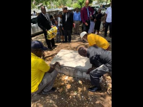 The vaunt with the remains of Carlton Thomas being sealed by workmen at the Content Cemetery, in St. James, on Sunday.