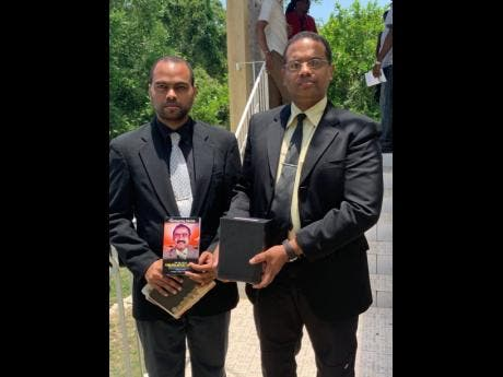 Christopher Thomas (left) and his brother, Carlos, with the urn bearing the remains of their father, Carlton Thomas, following Sunday's funeral at the Chatham Seventh-day Adventist Church in St James.