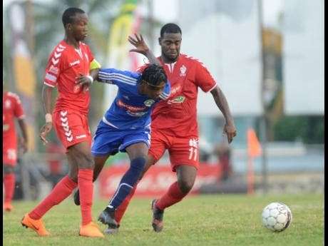 Mount Pleasant's Daniel Green (centre) drives past UWI FC defenders Rochane Smith (left) and Dwayne Smith during the first leg of their quarter-final match at the Tony Spaullding Sports Complex on March 24, 2019.