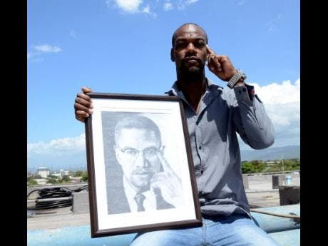 Rudolph Francis, a self-taught artist, poses with one of his pieces.