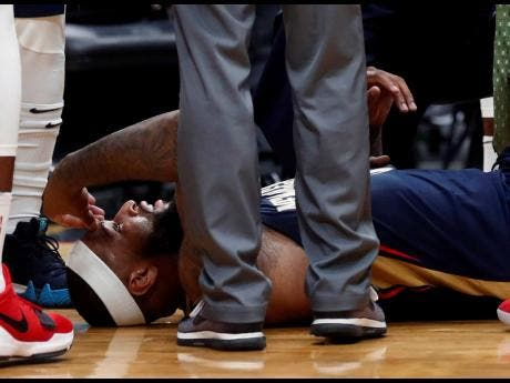 In this Jan. 26, 2018, file photo, then-New Orleans Pelicans centre DeMarcus Cousins lies on the court while being tended to after an injury during the second half of an NBA basketball game against the Houston Rockets in New Orleans.