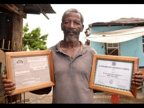 Alva Rowe shows his awards for cattle husbandry (left) and for first aid and CPR.