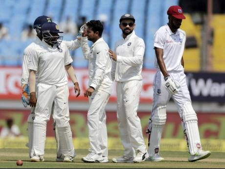Indian cricketer Kuldeep Yadav (without cap) celebrates after dismissing West Indies' Roston Chase during the third day of the first cricket Test match between the teams in Rajkot, India, on October 6, 2018.