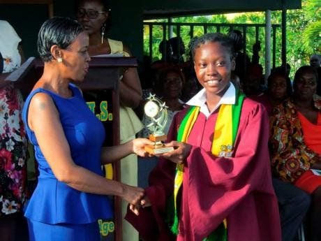 Valentina Wisdom (right) accepts an award from Francine Francis-Chin at her graduation ceremony last month.