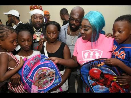 Spice (second right) and fellow entertainers Richie Stephens (third right) and Elephant Man (third left) hand out backpacks at the back-to- school treat.
