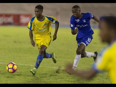 Clarendon College's Lamar Walker (left), dribbles by Kingston College's Trayvon Reid, during last season's ISSA Olivier Shield clash at the National Stadium on Saturday, December 8, 2018.