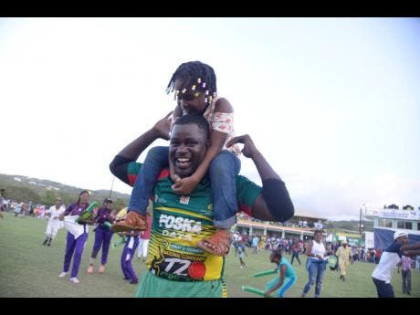 Gayle Cricket Club's Mickail Downer celebrates with his daughter  Mahelea after winning the SDC/Wray & Nephew community  cricket final yesterday.