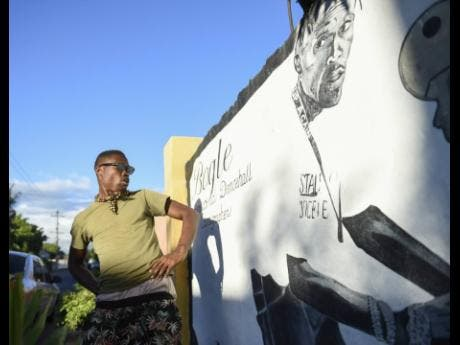 Michael Roses dances before a mural of dancing legend Bogle on Lincoln Crescent in the vicinity of Roses Corner.