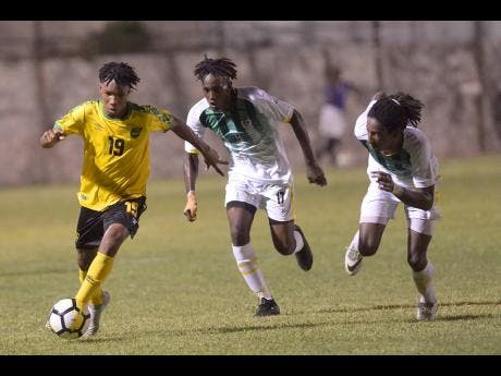 Jamaica's Tyreek Magee (left) dribbles while under pressure from Dominican defenders George Usher (centre) and Jolly Fitz during their Concacaf U-23 Olympic qualifier at the Anthony Spaulding Sports Complex in Kingston, Jamaica, on Wednesday, July 17.