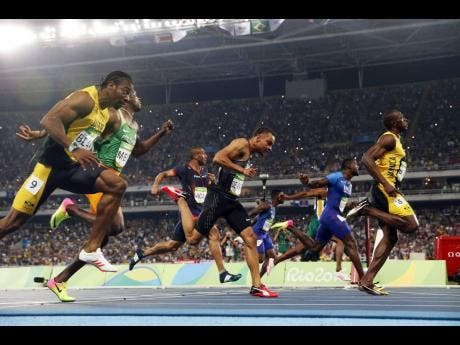 Usain Bolt of Jamaica (right) wins gold in the men's 100m final, for the third time, during the Summer Olympics in Rio de Janeiro on Sunday, August 14, 2016.