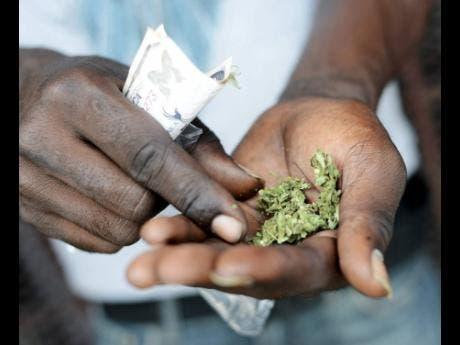 A man prepares a ganja spliff on the streets of downtown, Kingston. File