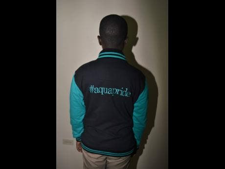 A student shows off one of the #aquapride jackets.