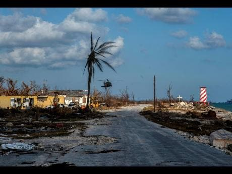 A helicopter flies over the village of High Rock, Grand Bahama, yesterday after delivering emergency supplies in the aftermath of Hurricane Dorian.