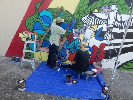 Nicola Byron (right) and Clinton Brown work on the mural.