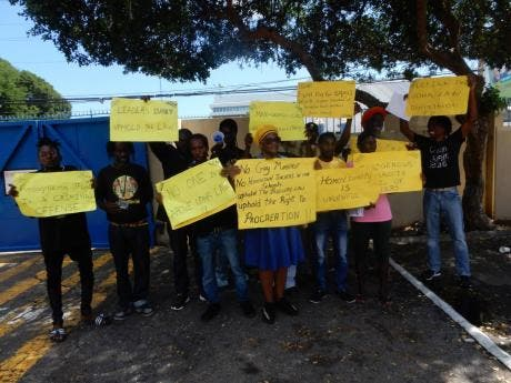 Members of the Kingdom of Debre Zeit group show their placards at the Gleaner Company Media Limited's office yesterday.