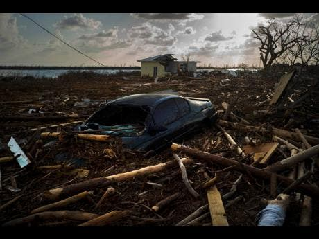 A car is sunk in the debris caused by Hurricane Dorian in Mclean's Town, Grand Bahama, Bahamas.