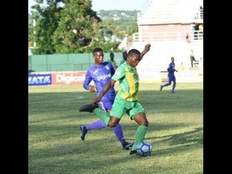 Kingston College's Ranaldo Robinson (left) challenges Excelsior High's Tariq Duffus for the ball during their ISSA/Digicel Manning Cup match at Montego Bay Sports Complex on  Saturday, September  7.