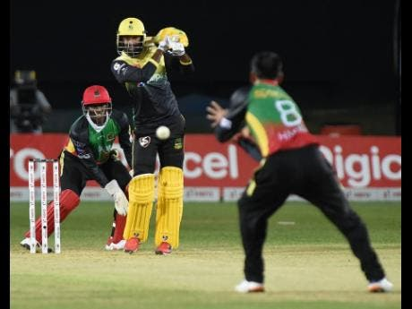 Imran Khan (centre) from the Jamaica Tallawahs is bowled and caught by Mohammed Hafeez (right) from St.Kitts and Nevis Patriots, while the wicketkeeper Devon Thomas (left) looks on.
