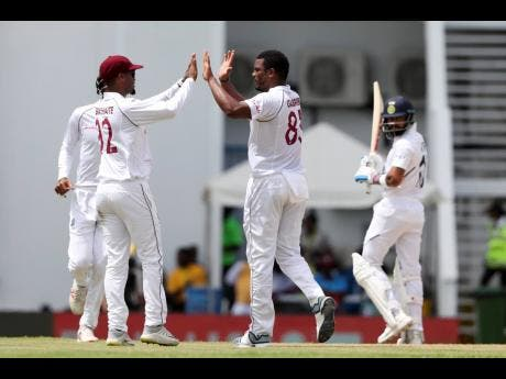 Windies' bowler Kraigg Brathwaite (left) and teammate Shannon Gabriel celebrate the dismissal of India captain Virat Kohli (right) during day one of their first Test cricket match at the Sir Vivian Richards Stadium in North Sound, Antigua and Barbuda, on Thursday, August 22, 2019.