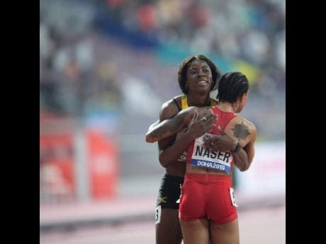 Bronze medalist Shericka Jackson (left) of Jamaica  embraces  the new women's 400m World champion Salwa Eid Naser of Bahrain after the final of the event in Doha, Qatar yesterday.
