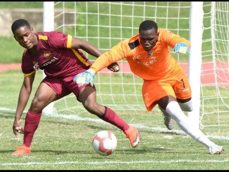 Tarrant High goalkeeper Jonathan Currie (right) getting to the ball ahead of  Zhavier Lynch of  Wolmer's Boys during yesterday's ISSA/Digicel Manning Cup match at the  Stadium East field. Wolmer's won 3-0.